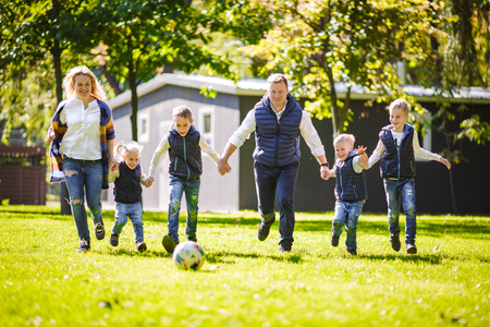 The theme family outdoor activities. big friendly Caucasian family of six mom dad and four children playing football, running with the ball on lawn, green grass lawn near the house on a sunny day. Standard-Bild - 115333741