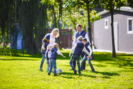 The theme family outdoor activities. big friendly Caucasian family of six mom dad and four children playing football, running with the ball on lawn, green grass lawn near the house on a sunny day. Standard-Bild - 115333943