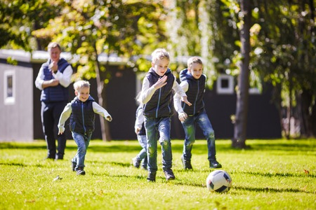 The theme family outdoor activities. big friendly Caucasian family of six mom dad and four children playing football, running with the ball on lawn, green grass lawn near the house on a sunny day. Standard-Bild - 115333977