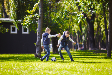 The theme family outdoor activities. big friendly Caucasian family of six mom dad and four children playing football, running with the ball on lawn, green grass lawn near the house on a sunny day.