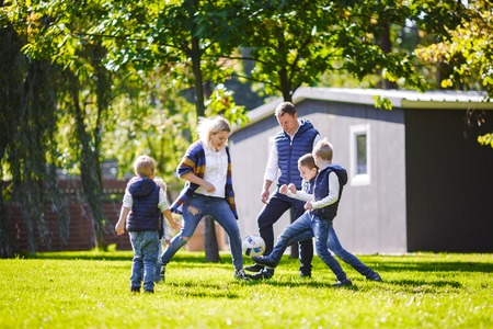 The theme family outdoor activities. big friendly Caucasian family of six mom dad and four children playing football, running with the ball on lawn, green grass lawn near the house on a sunny day. Standard-Bild - 115334032
