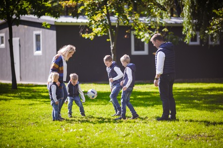 The theme family outdoor activities. big friendly Caucasian family of six mom dad and four children playing football, running with the ball on lawn, green grass lawn near the house on a sunny day. Standard-Bild - 115334146