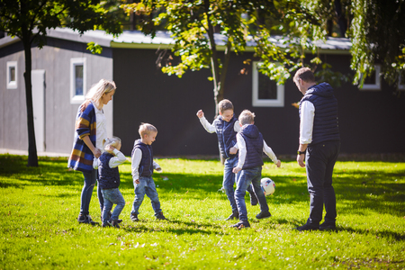 The theme family outdoor activities. big friendly Caucasian family of six mom dad and four children playing football, running with the ball on lawn, green grass lawn near the house on a sunny day. Standard-Bild - 115334151