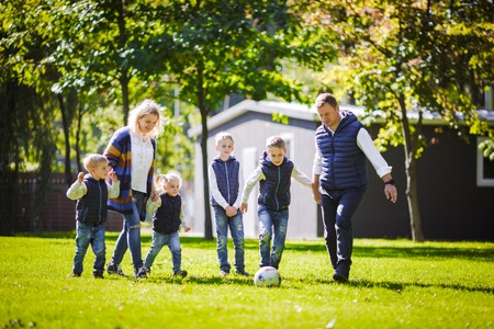 The theme family outdoor activities. big friendly Caucasian family of six mom dad and four children playing football, running with the ball on lawn, green grass lawn near the house on a sunny day. Standard-Bild - 115334192