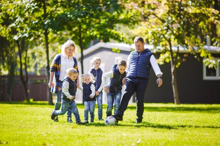 The theme family outdoor activities. big friendly Caucasian family of six mom dad and four children playing football, running with the ball on lawn, green grass lawn near the house on a sunny day. Standard-Bild - 115334244