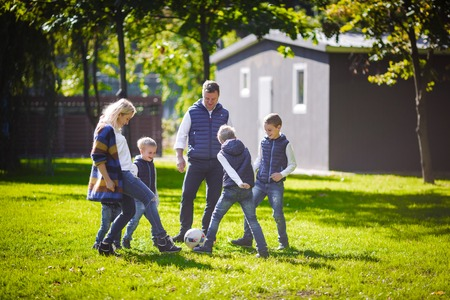 The theme family outdoor activities. big friendly Caucasian family of six mom dad and four children playing football, running with the ball on lawn, green grass lawn near the house on a sunny day. Standard-Bild - 115334255