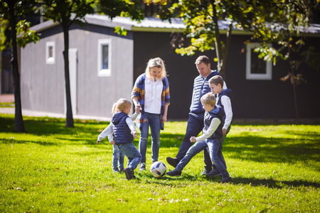 The theme family outdoor activities. big friendly Caucasian family of six mom dad and four children playing football, running with the ball on lawn, green grass lawn near the house on a sunny day. Standard-Bild - 115334259