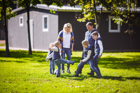 The theme family outdoor activities. big friendly Caucasian family of six mom dad and four children playing football, running with the ball on lawn, green grass lawn near the house on a sunny day. Standard-Bild - 115334268