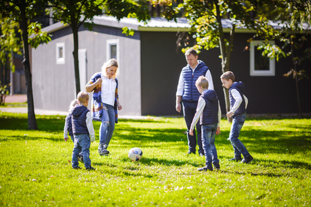 The theme family outdoor activities. big friendly Caucasian family of six mom dad and four children playing football, running with the ball on lawn, green grass lawn near the house on a sunny day. Standard-Bild - 115334315