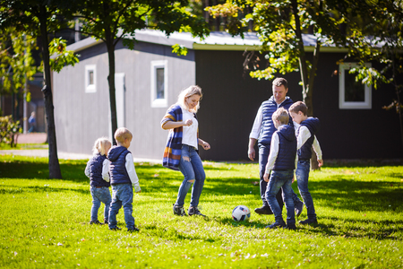 The theme family outdoor activities. big friendly Caucasian family of six mom dad and four children playing football, running with the ball on lawn, green grass lawn near the house on a sunny day. Standard-Bild - 115334322