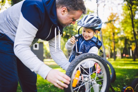 Fathers day Caucasian dad and 5 year old son in the backyard near the house on the green grass on the lawn repairing a bicycle, pumping a bicycle wheel. Dad teaches how to repair a childs bike. Stock Photo