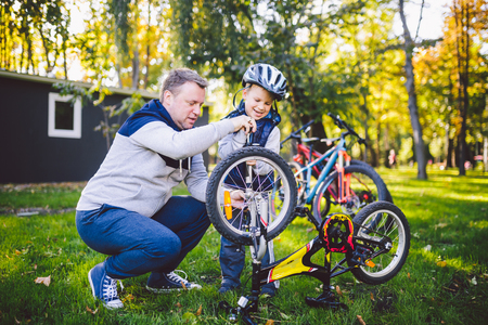 Father's day Caucasian dad and 5 year old son in the backyard near the house on the green grass on the lawn repairing a bicycle, pumping a bicycle wheel. Dad teaches how to repair a child's bike. Standard-Bild - 115334356
