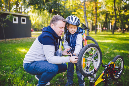 Father's day Caucasian dad and 5 year old son in the backyard near the house on the green grass on the lawn repairing a bicycle, pumping a bicycle wheel. Dad teaches how to repair a child's bike. Standard-Bild - 115334362