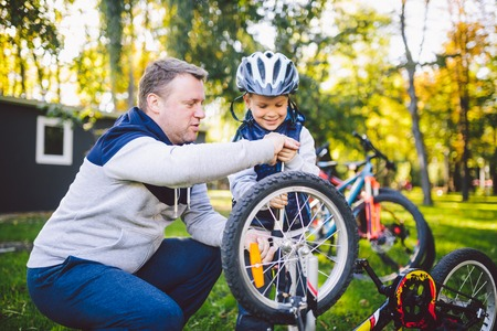 Father's day Caucasian dad and 5 year old son in the backyard near the house on the green grass on the lawn repairing a bicycle, pumping a bicycle wheel. Dad teaches how to repair a child's bike. Standard-Bild - 115334440