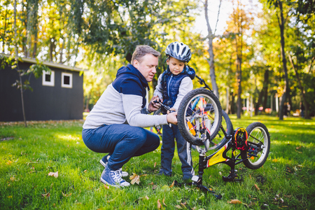 Father's day Caucasian dad and 5 year old son in the backyard near the house on the green grass on the lawn repairing a bicycle, pumping a bicycle wheel. Dad teaches how to repair a child's bike. Standard-Bild - 115334636