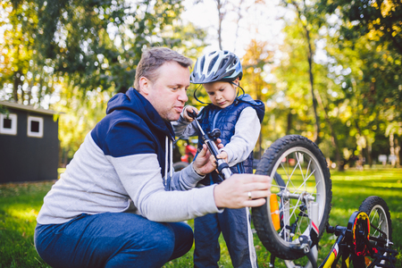 Father's day Caucasian dad and 5 year old son in the backyard near the house on the green grass on the lawn repairing a bicycle, pumping a bicycle wheel. Dad teaches how to repair a child's bike. Standard-Bild - 115334661