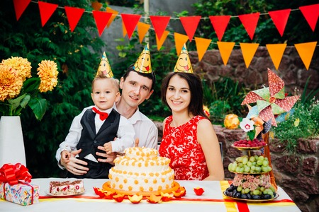 Children birthday theme. family of three Caucasian people sitting in backyard of the house at a festive decorated table in funny hats and caps on their heads. Joy and happiness cake and pastry snack.