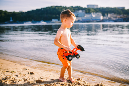Caucasian child boy playing toy red tractor, excavator on a sandy beach by the river in red shorts at sunset day. Standard-Bild - 115334689