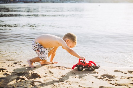 Caucasian child boy plays toy red tractor, excavator on sandy beach by the river in shorts at sunset day. Standard-Bild - 115334690