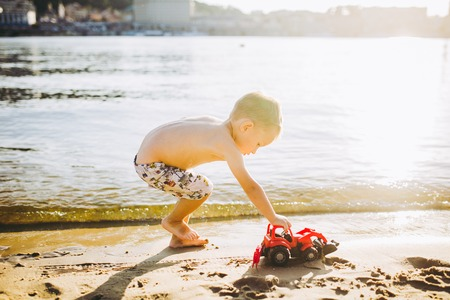 Caucasian child boy plays toy red tractor, excavator on sandy beach by the river in shorts at sunset day. Standard-Bild - 115334691