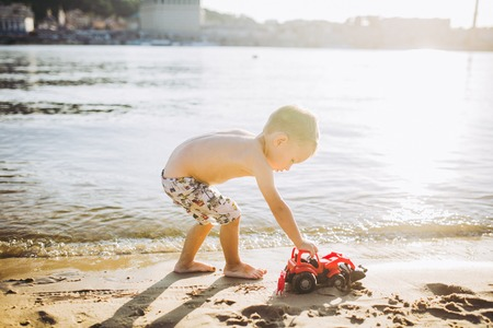 Caucasian child boy plays toy red tractor, excavator on sandy beach by the river in shorts at sunset day. Standard-Bild - 115334692
