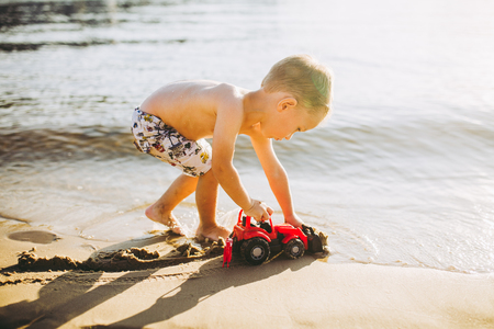 Caucasian child boy plays toy red tractor, excavator on sandy beach by the river in shorts at sunset day.