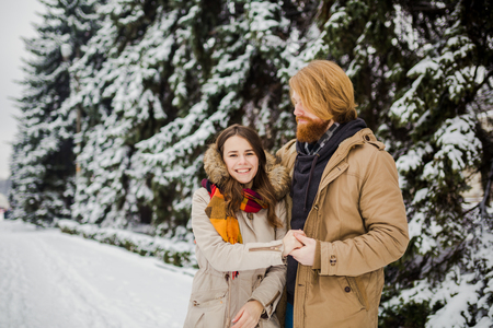 Young Caucasian boy and girl in love heterosexual couple have a date outdoors in a winter park on the background of a snowy conifer standing in an embrace. Man hugging woman valentines day Imagens