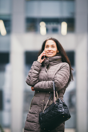 Business lady. Beautiful caucasian brunette woman uses technology mobile phone pink against background of the plastic facade of the window. The girl is calling, talking on the phone. Theme Business. 写真素材
