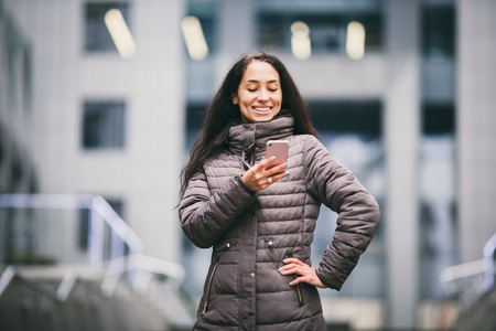 Business lady. Beautiful caucasian brunette woman uses technology mobile phone pink against background of the plastic facade of the window. The girl is calling, talking on the phone. Theme Business. Stock Photo