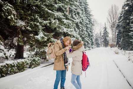 Date young couple in winter. Young Caucasian man with beard and long hair holding in hands the hands of girl with knitted gloves and warming and kissing them in snow park in winter is Valentines Day. Standard-Bild - 115334721