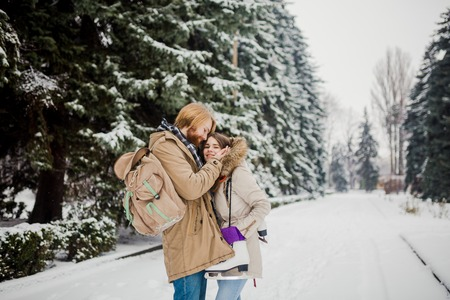 Date young couple in winter. Young Caucasian man with beard and long hair holding in hands the hands of girl with knitted gloves and warming and kissing them in snow park in winter is Valentines Day. Standard-Bild - 115334722