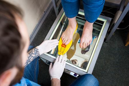Orthopädie und Medizin. Junger kaukasischer Arzt übergibt Mann Tattoo Latexhandschuhe Größenmessung Form des Fußes für die Herstellung der individuellen orthopädischen Einlegesohle. Plattfuß und Fußkrankheiten. Standard-Bild
