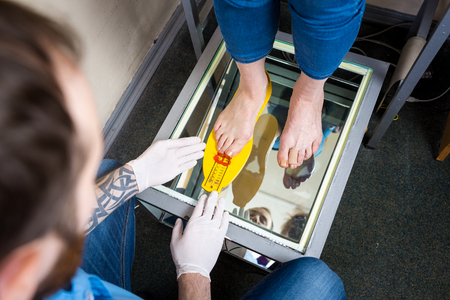 Ortopedia y medicina. Joven médico caucásico manos hombre tatuaje látex guantes tamaño medida forma del pie para la fabricación de plantilla ortopédica individual. Enfermedades del pie plano y del pie. Foto de archivo