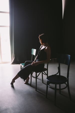 The social theme female loneliness pain suffering. Abastration male violence family. A young beautiful Caucasian woman in black clothes sitting on three chairs in large dark room. Srach and despair. Standard-Bild - 115334724