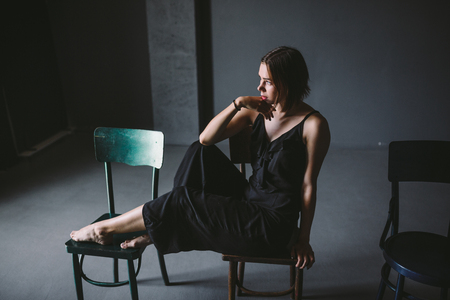 The social theme female loneliness pain suffering. Abastration male violence family. A young beautiful Caucasian woman in black clothes sitting on three chairs in large dark room. Srach and despair.