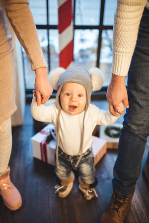 Funny little baby boy 1 year old learning walk home in winter in a decorated New Year house. Young family dad and mom hold by the hands of his son in the loft interior wooden floor near the window. Фото со стока