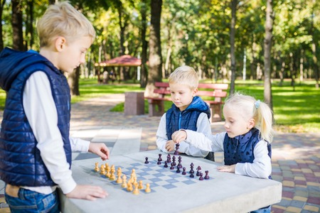 The topic children learning, logical development, mind and math, miscalculation moves advance. large family brothers and sister Caucasian boys and girl playing chess park bright sunny weather autumn. Stock fotó