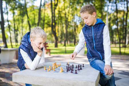 The topic is children learning, logical development, mind math, miscalculation moves advance. Big family two brothers Caucasian boys playing chess in the park in bright sunny weather in the autumn.