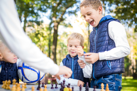 The topic children learning, logical development, mind and math, miscalculation moves advance. large family brothers and sister Caucasian boys and girl playing chess park bright sunny weather autumn. Imagens - 113472173