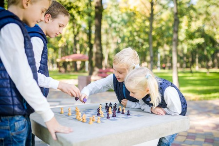 The topic children learning, logical development, mind and math, miscalculation moves advance. large family brothers and sister Caucasian boys and girl playing chess park bright sunny weather autumn. 免版税图像