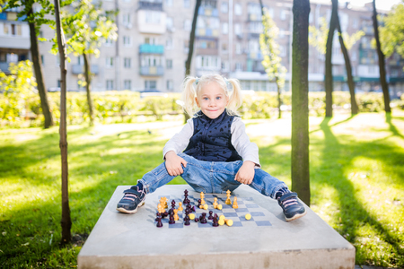 Funny Caucasian baby girl blonde does not want learn, does not want to school, want to play, laugh and indulge. child with hair ponytail sits table legs forward, spread out, mess, tabletop logic game.
