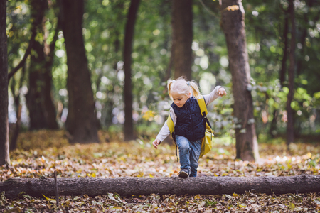 The theme children outdoor activities. Funny little baby Caucasian blond girl walks through forest overcoming obstacles, tree fell, log. Baby hiking big funny backpack in autumn forest park.