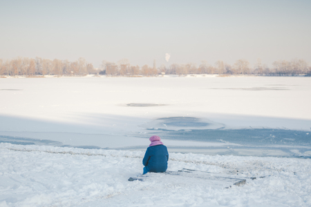 The theme is old age, loneliness and retirement age. Social theme. An old man woman sits with his back and looks at the frozen lake and thinks. Death death and end of life.