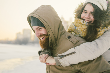 Theme New Year Christmas Mood Winter Snow Holidays Valentine Day. Young Caucasian couple lovers joy, laughter fooling water in city park. man holds woman on shoulders as backpack. Stockfoto