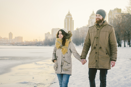 Theme Christmas holidays winter new year. Young stylish Caucasian loving couple Heteresexual walking on the shore of a frozen lake. Date. Valentines Day in winter at sunset. Love and Romance Theme.