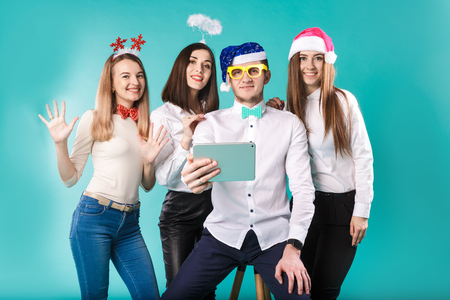 New Year theme Christmas winter office company employees. Group 4 young Caucasian people business smile holiday funny hats accessories glasses take photo yourself selfie tablet blued background. Standard-Bild - 115334479