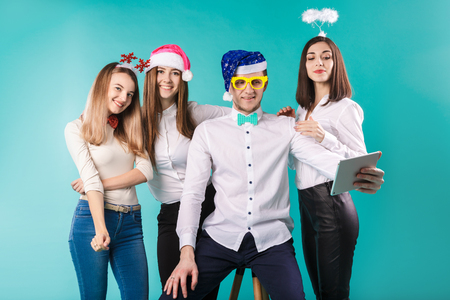 New Year theme Christmas winter office company employees. Group 4 young Caucasian people business smile holiday funny hats accessories glasses take photo yourself selfie tablet blued background. Standard-Bild - 115334483