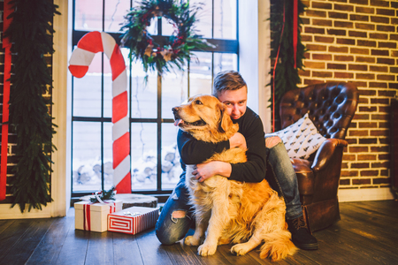 The theme is the friendship of man and animal. Caucasian young male and pet dog breed Labrador Golden Retriever at home inside in winter. Christmas time, New Year holidays. Standard-Bild - 115334582