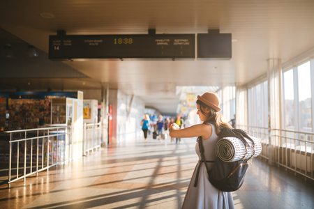 Theme travel public transport. young woman standing with back in dress and hat behind backpack and camping equipment for sleeping, insulating mat looks schedule on scoreboard airport station sunny day. Standard-Bild