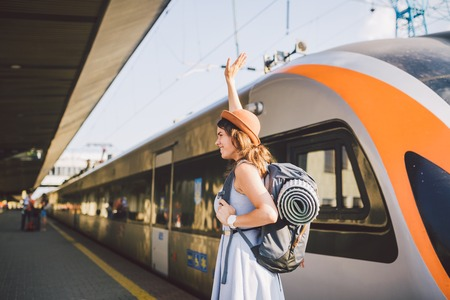 Theme transportation and travel. Portrait of young Caucasian woman with toothy smile standing at train station background with backpack waving hello while hand up, joy sign in dress and hat in summer.